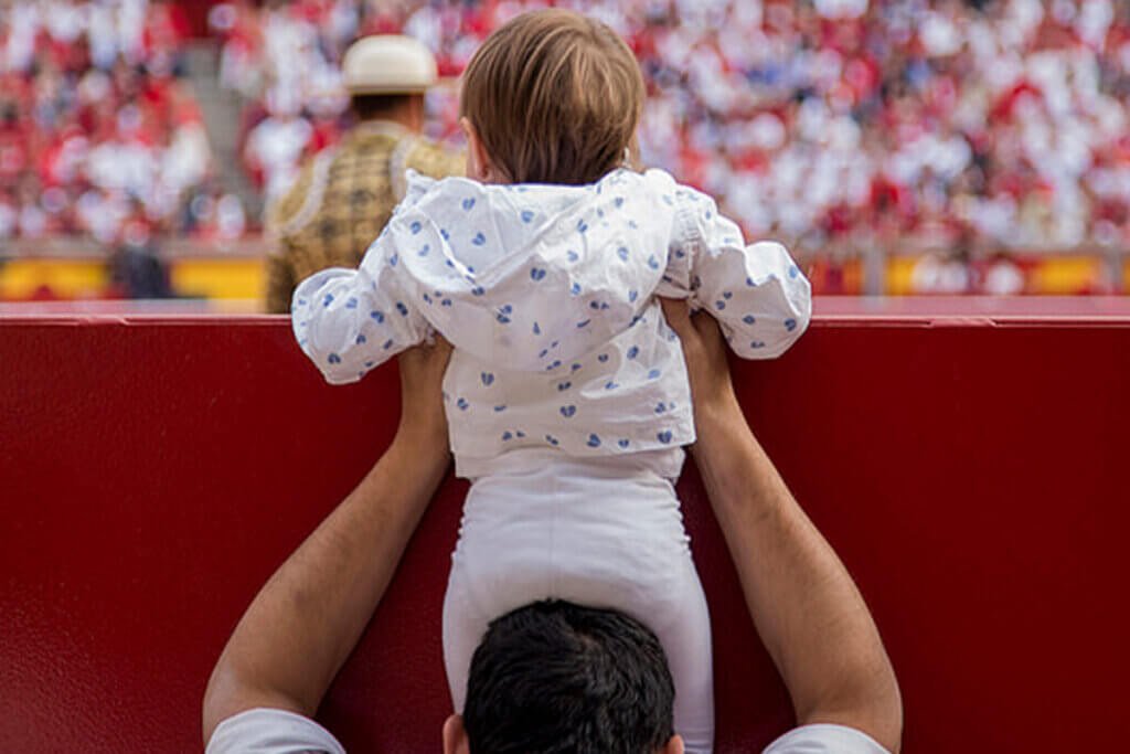 Kind auf den Schultern eines Mannes sieht beim Stierkampf zu