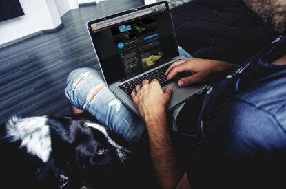 Mann mit Laptop auf dem Schoss