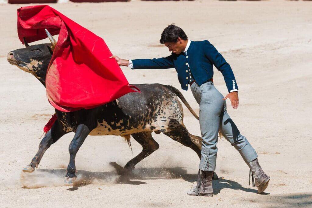 Matador wirft rotes Tuch nach einem Stier