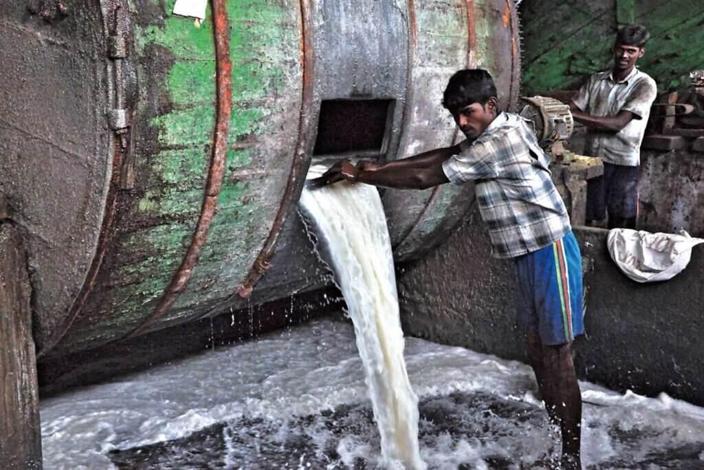 Indischer Mitarbeiter einer Gerberei steht in giftigem Chemiebad
