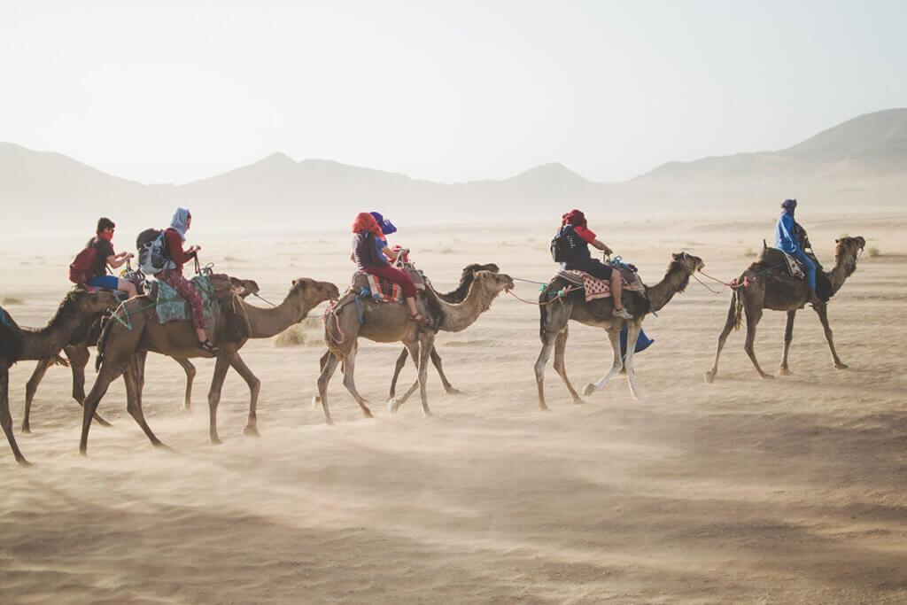 Karawane mit Touristen die auf Kamelen reiten