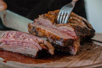 Fleisch auf Holzbrett wird angeschnitten