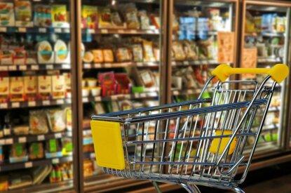 Einkaufswagen vor Supermarktregal