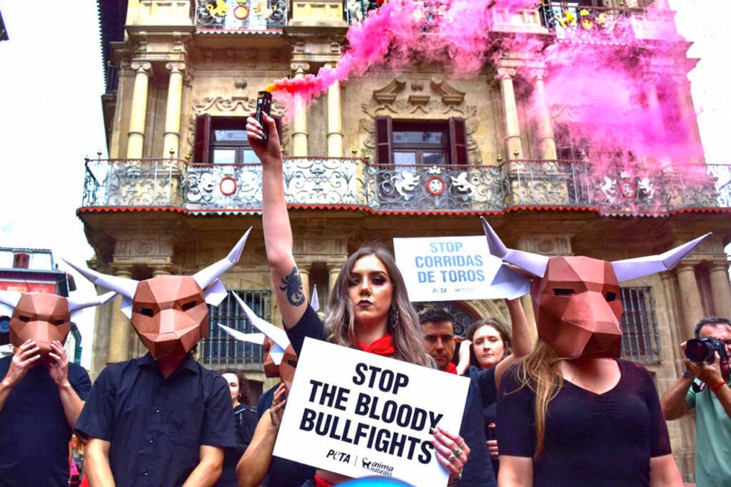 Aktivisten demonstrieren mit Schildern und Rauch gegen Stierkaempfe
