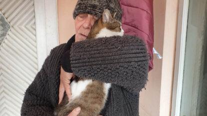 Mann haelt Katze im Arm