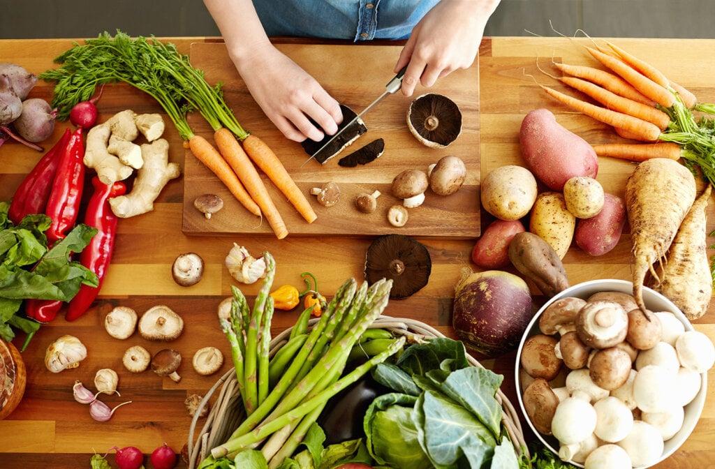 Person schneidet Gemüse auf dem Tisch