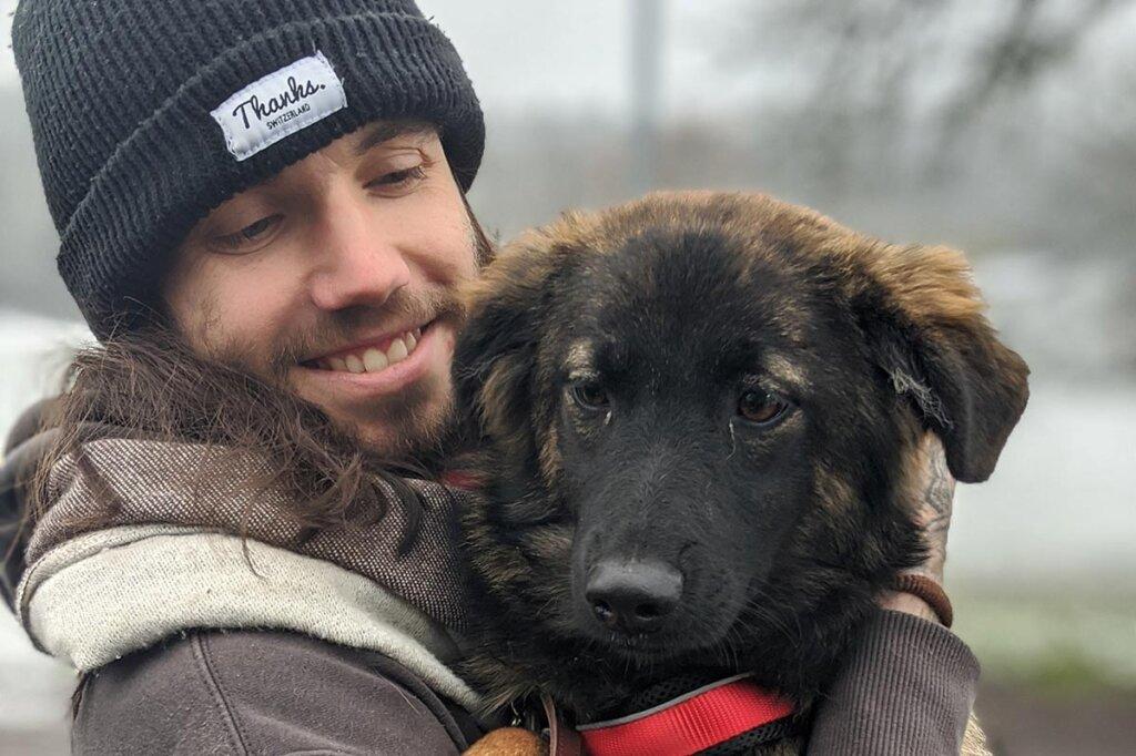 Mann haelt Hund im Arm