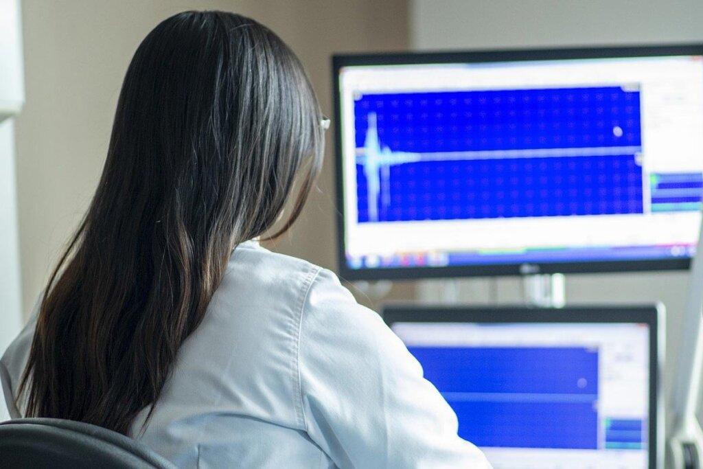 Frau im weißen Kittel sitzt am Computer