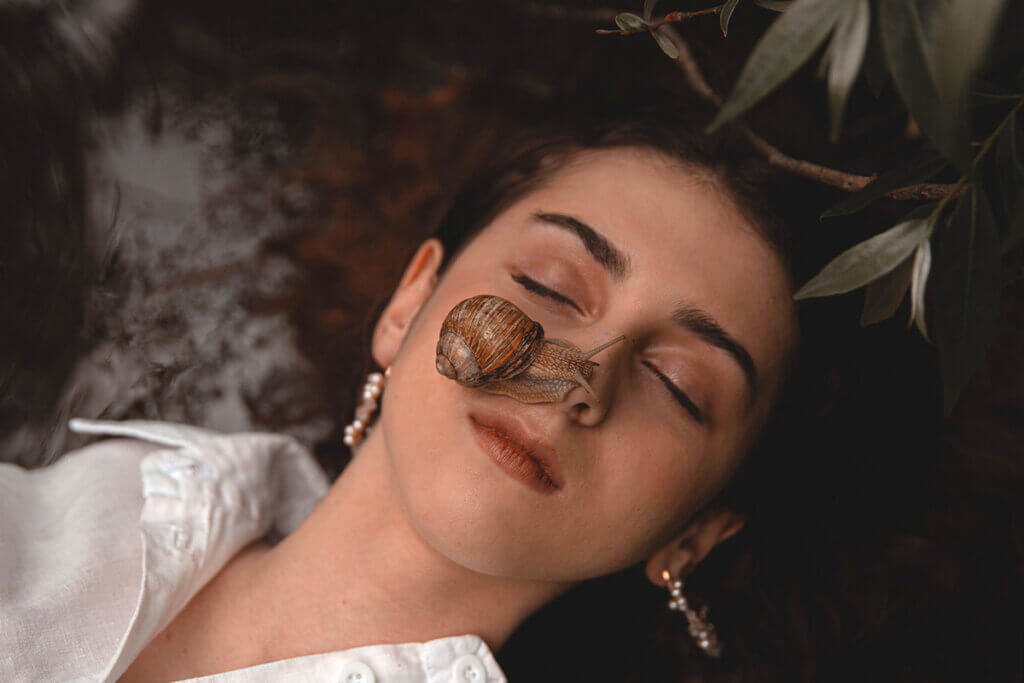 Frau mit Schnecke auf dem Gesicht