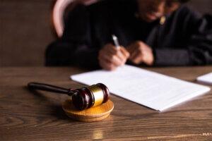 Richterin sitzt am Tisch mit einem Richterhammer