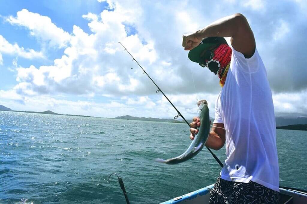 mann angelt und hat fisch mit haken in der hand
