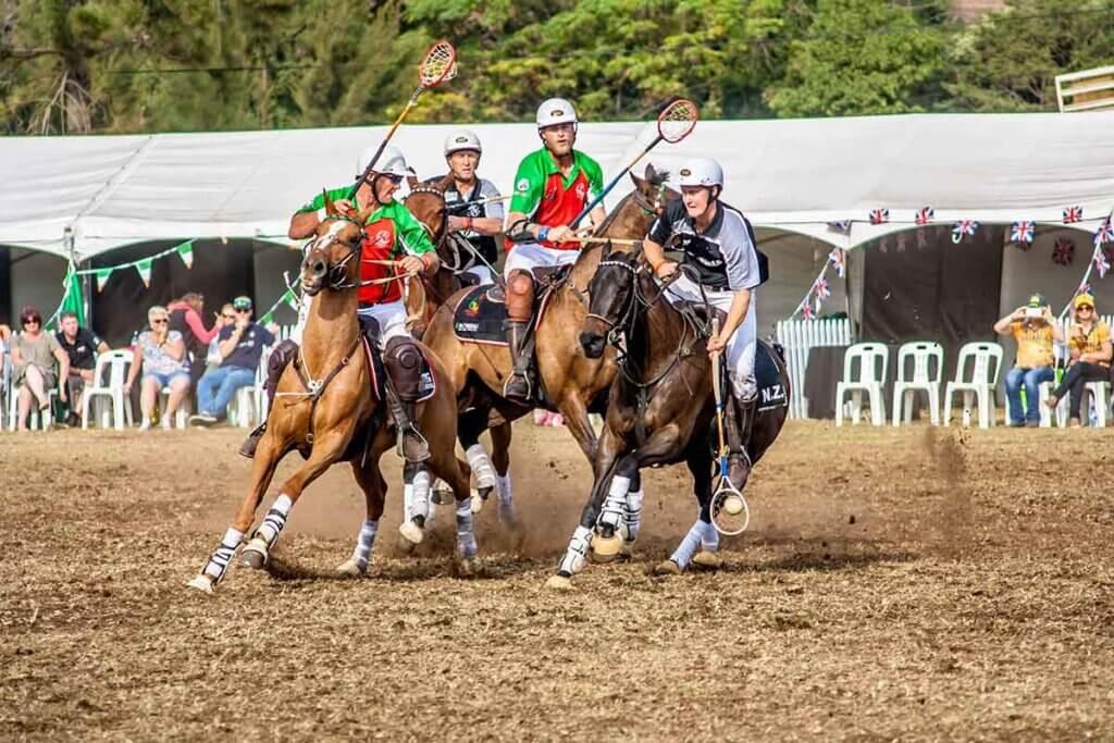 vier maenner spielen polo auf pferden